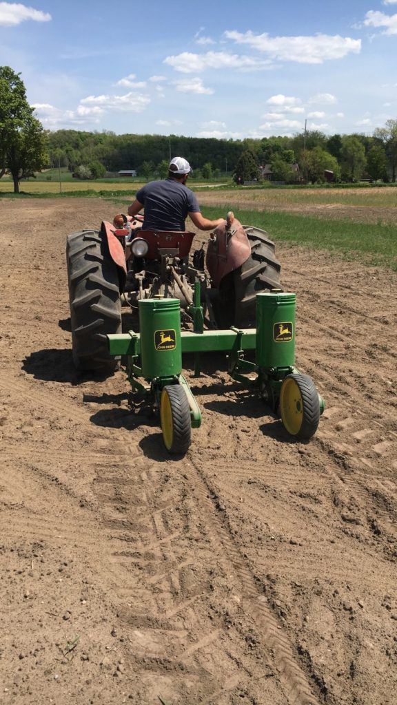 Zack using the 2 Row JD corn planter to put in our sweet corn patch....:}